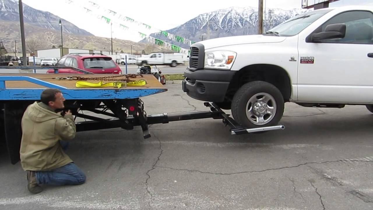 Technician With Wheel Lift Tow Truck On Service Call With A White Chevy Truck