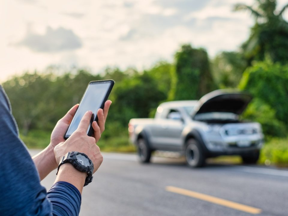 Person calling for roadside assistance help on cell phone for broken down truck