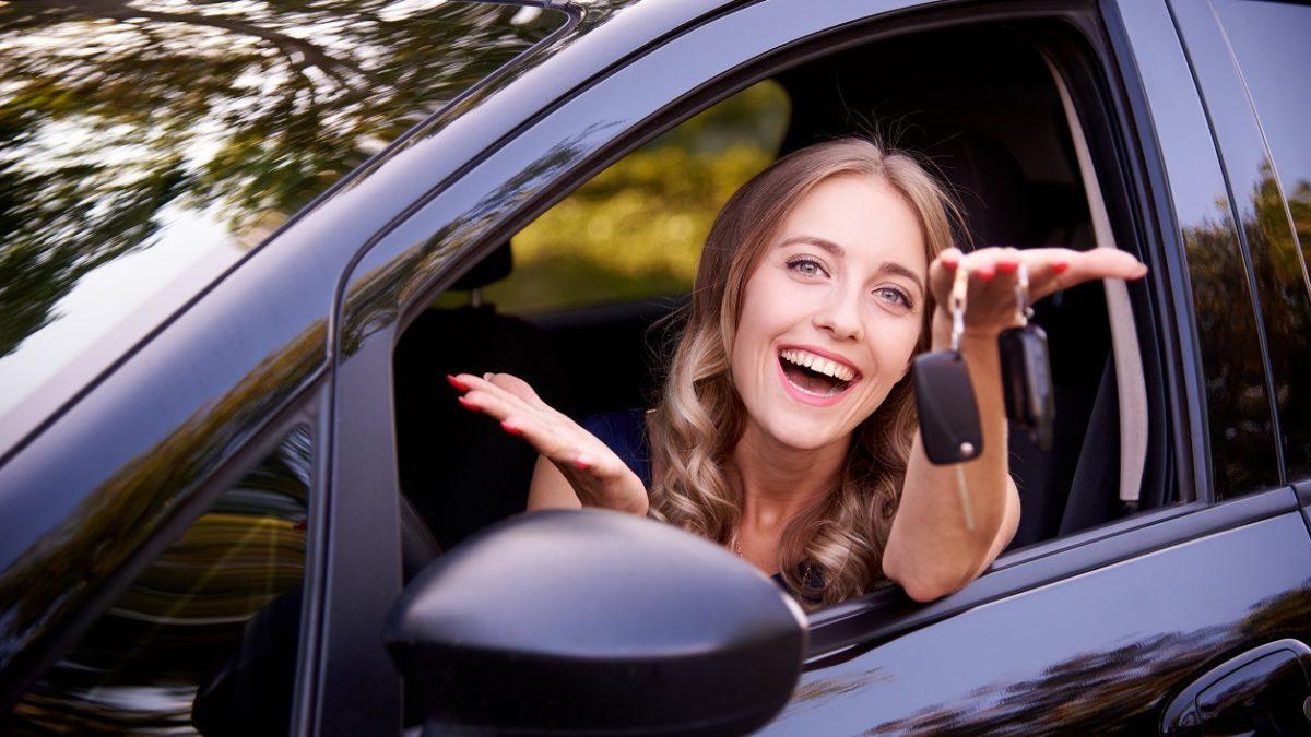 Teenage girl holding keys outside of car window